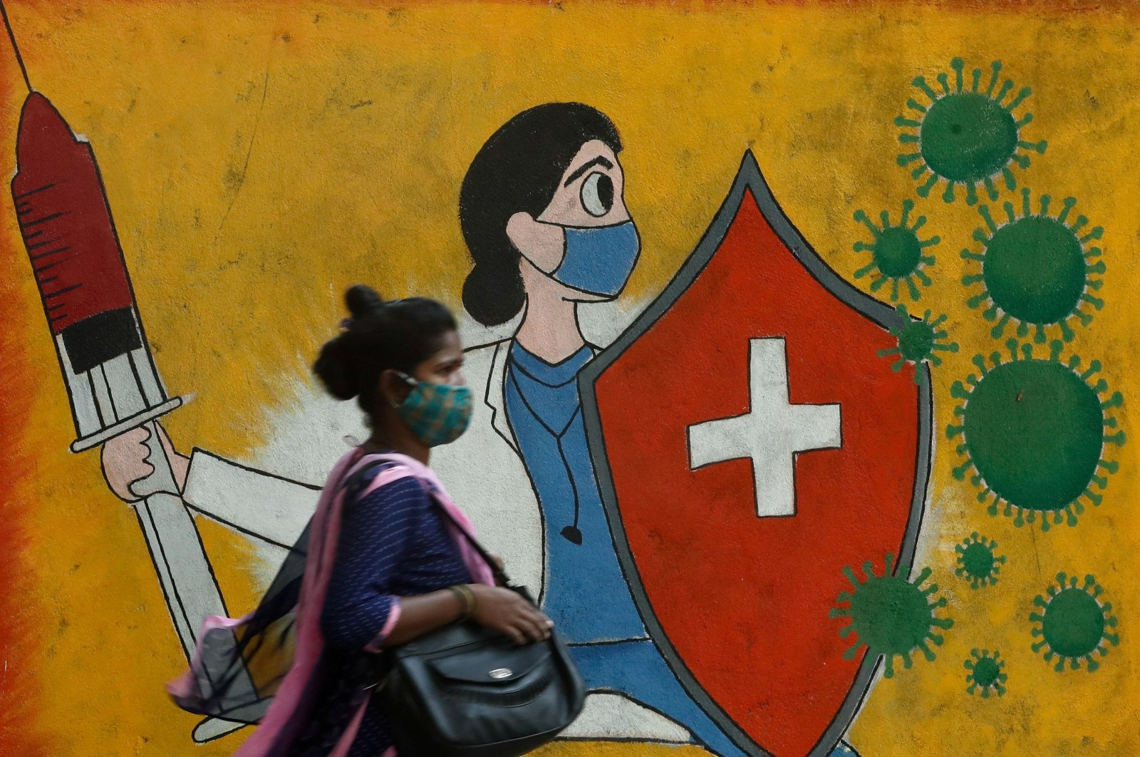 A woman walks past graffiti on a street depicting a health care worker fighting coronavirus cells, in Mumbai, India, May 10, 2021. (Reuters Photo)