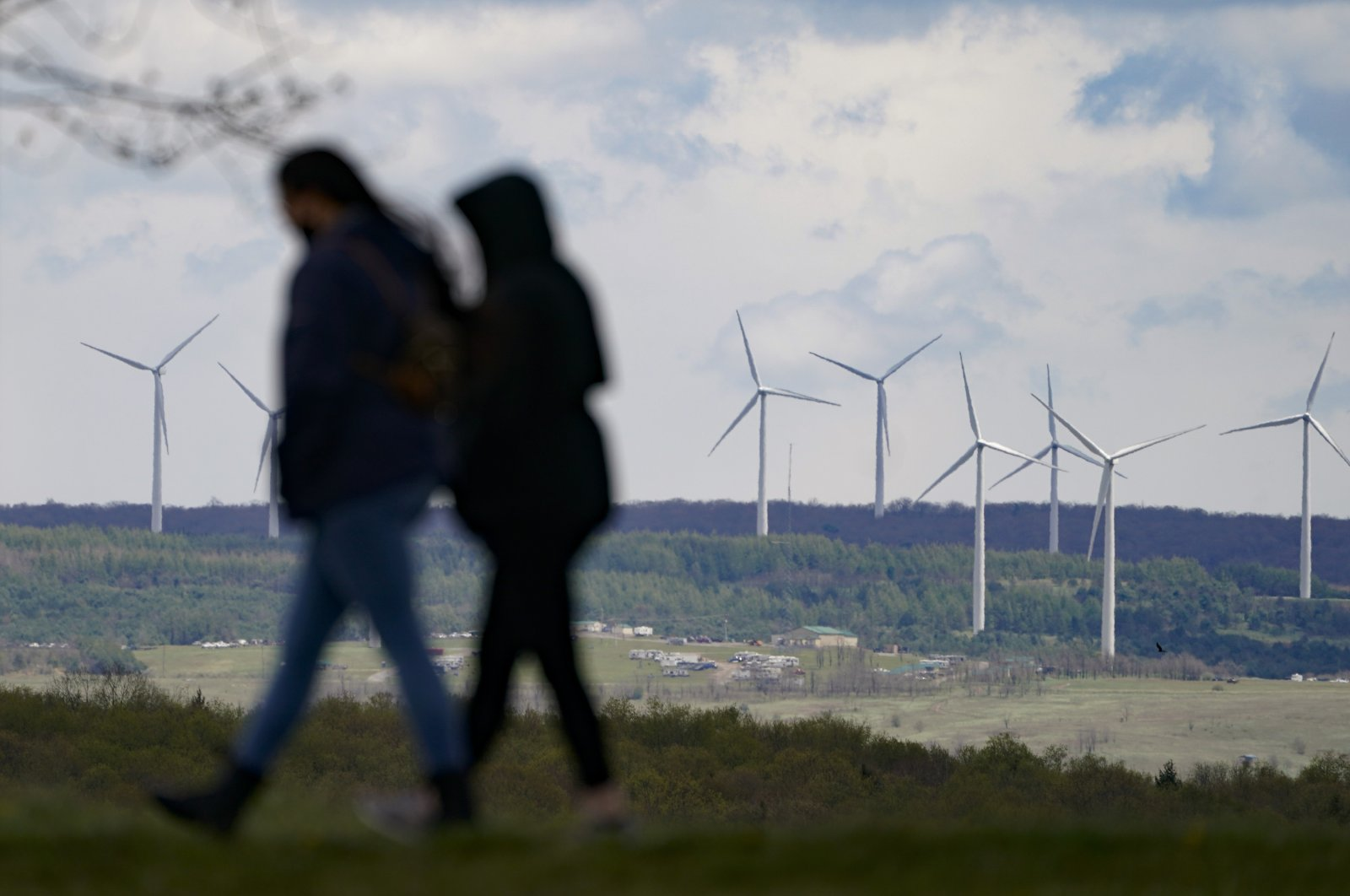 People are silhouetted as they stroll past power-generating wind turbines visible from a walking path at the Flight 93 National Memorial in Shanksville, Pennsylvania, U.S., May 8, 2021. (AP Photo)