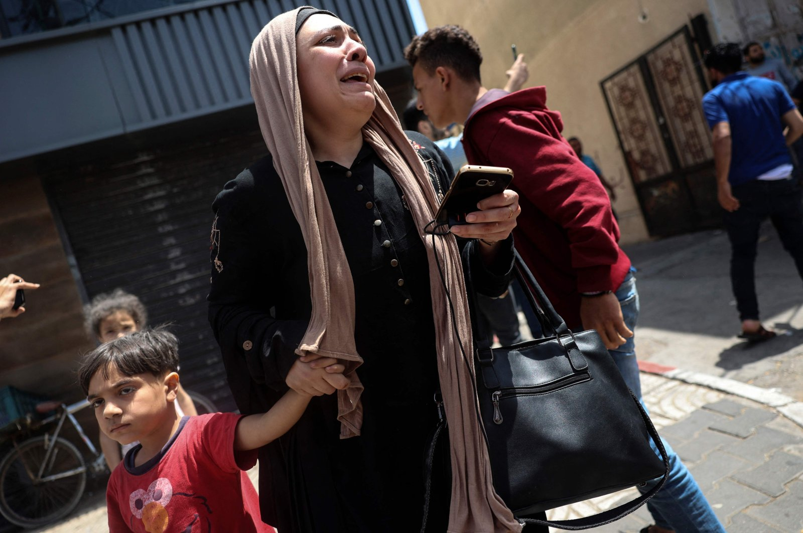 A Palestinian woman cries as she evacuates a building targeted by Israeli bombardment on Gaza City, Palestine, May 11, 2021. (AFP Photo)