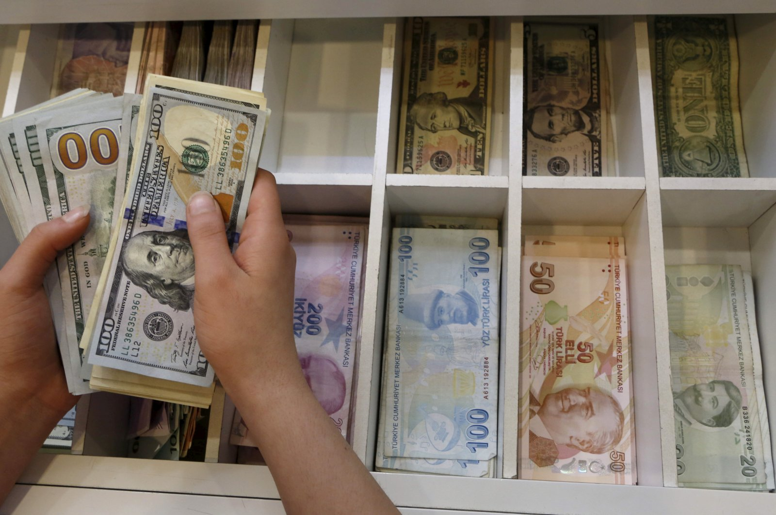 A money changer counts U.S. dollar bills, with Turkish lira banknotes in the background, at a currency exchange office in central Istanbul, Turkey, Aug. 21, 2015. (Reuters Photo)