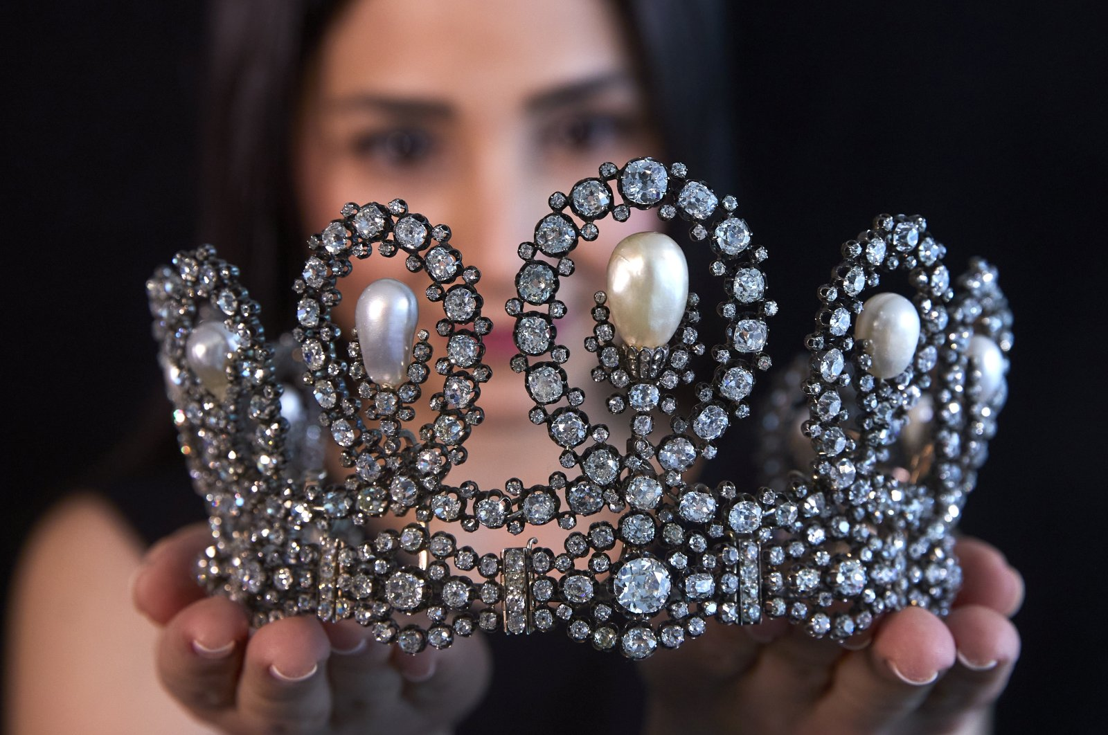 A staff holds a diamond and pearl tiara passed down through generations of the Italian royal family during a preview at Sotheby's before their auction in Geneva, Switzerland, May 6, 2021.  (Reuters Photo)