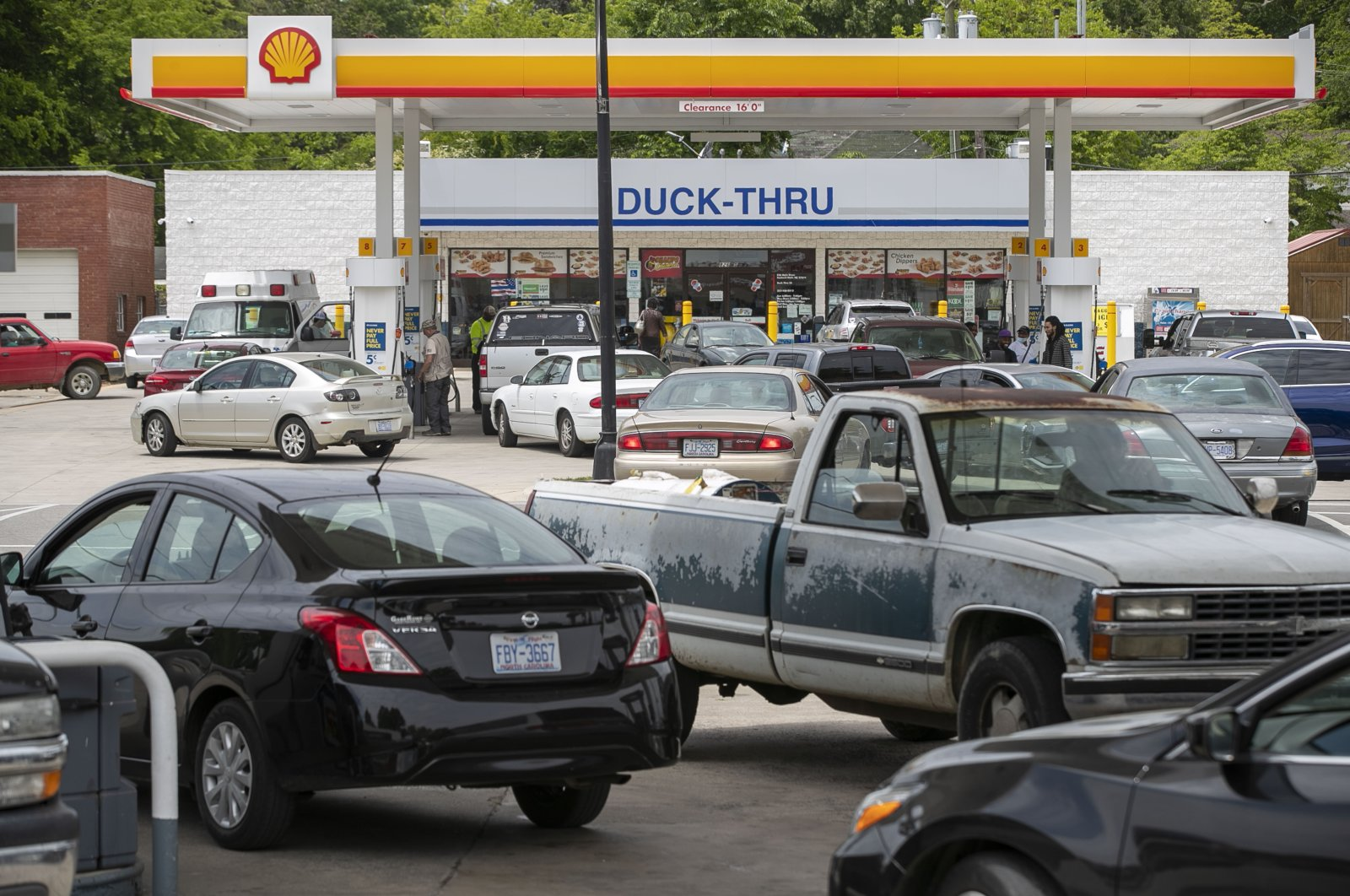 Customers fill up their vehicles with fuel at the Cupboard Food Store (foreground) and the Duck-Thru across in Scotland Neck, North Carolina, U.S., Tuesday, May 11, 2021. (AP Photo)