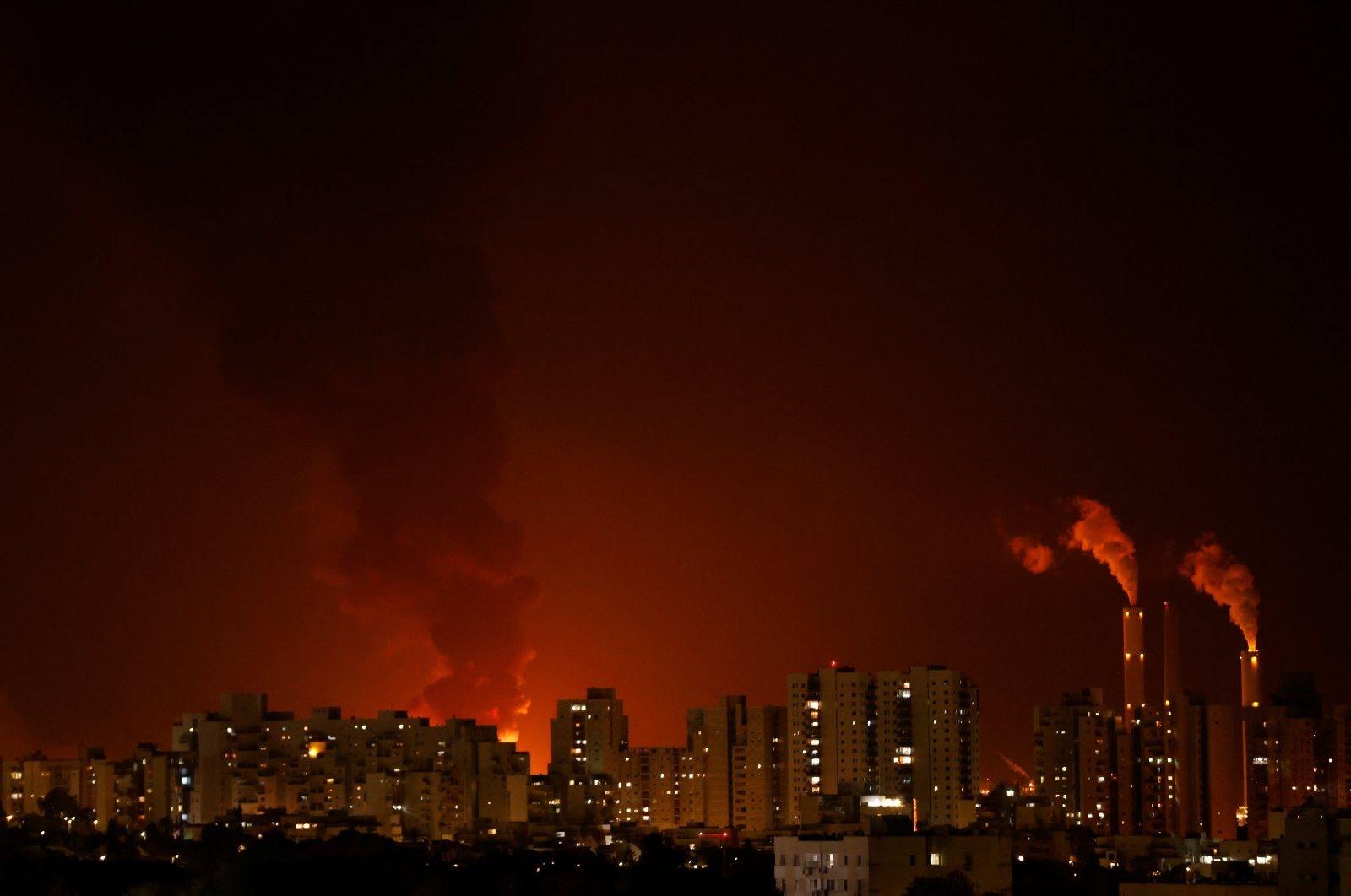 A general view shows residential buildings with large fire and smoke in the background, where officials said that a Gaza rocket hit an Israeli energy pipeline near Ashkelon, Israel, May 11, 2021. (Reuters Photo)