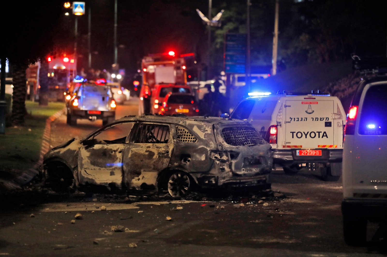 Israeli border police vehicles drive past an extinguished burnt vehicle in Lod near Tel Aviv, on May 11, 2021 (AFP Photo)