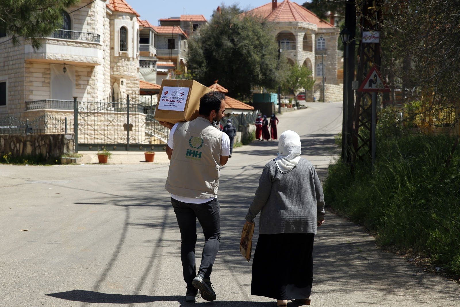 A volunteer from the Humanitarian Aid Foundation (IHH) carries an aid package delivered to an elderly woman, in Beirut, Lebanon, May 7, 2021. (AA PHOTO)