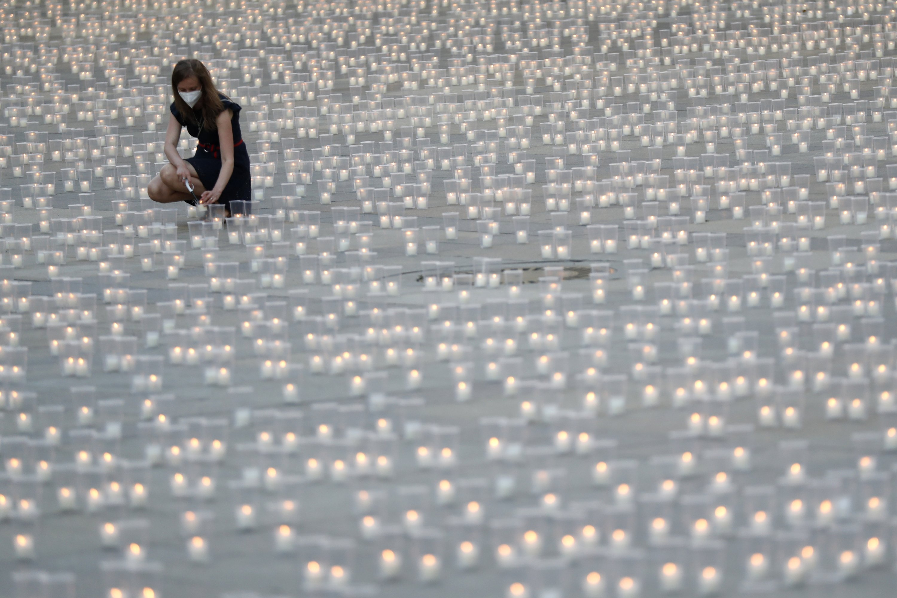 A woman lights a candle to commemorate victims of the COVID-19 pandemic at the Prague Castle in Prague, Czech Republic, May 10, 2021. (AP Photo)