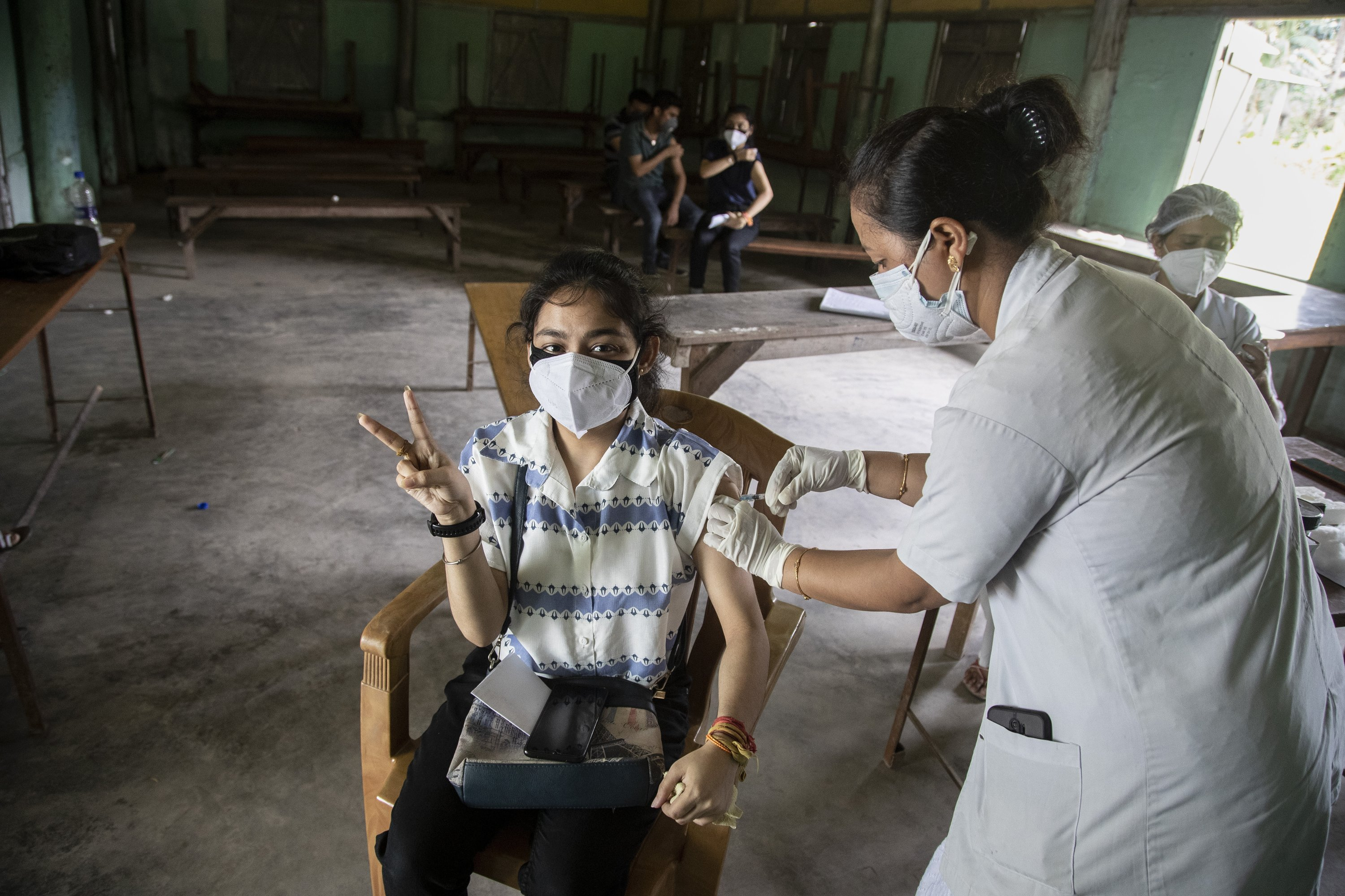 An Indian woman getting vaccinated with a dose of COVAXIN against the coronavirus gestures to the camera in Gauhati, Assam, India, May 10, 2021. (AP Photo)
