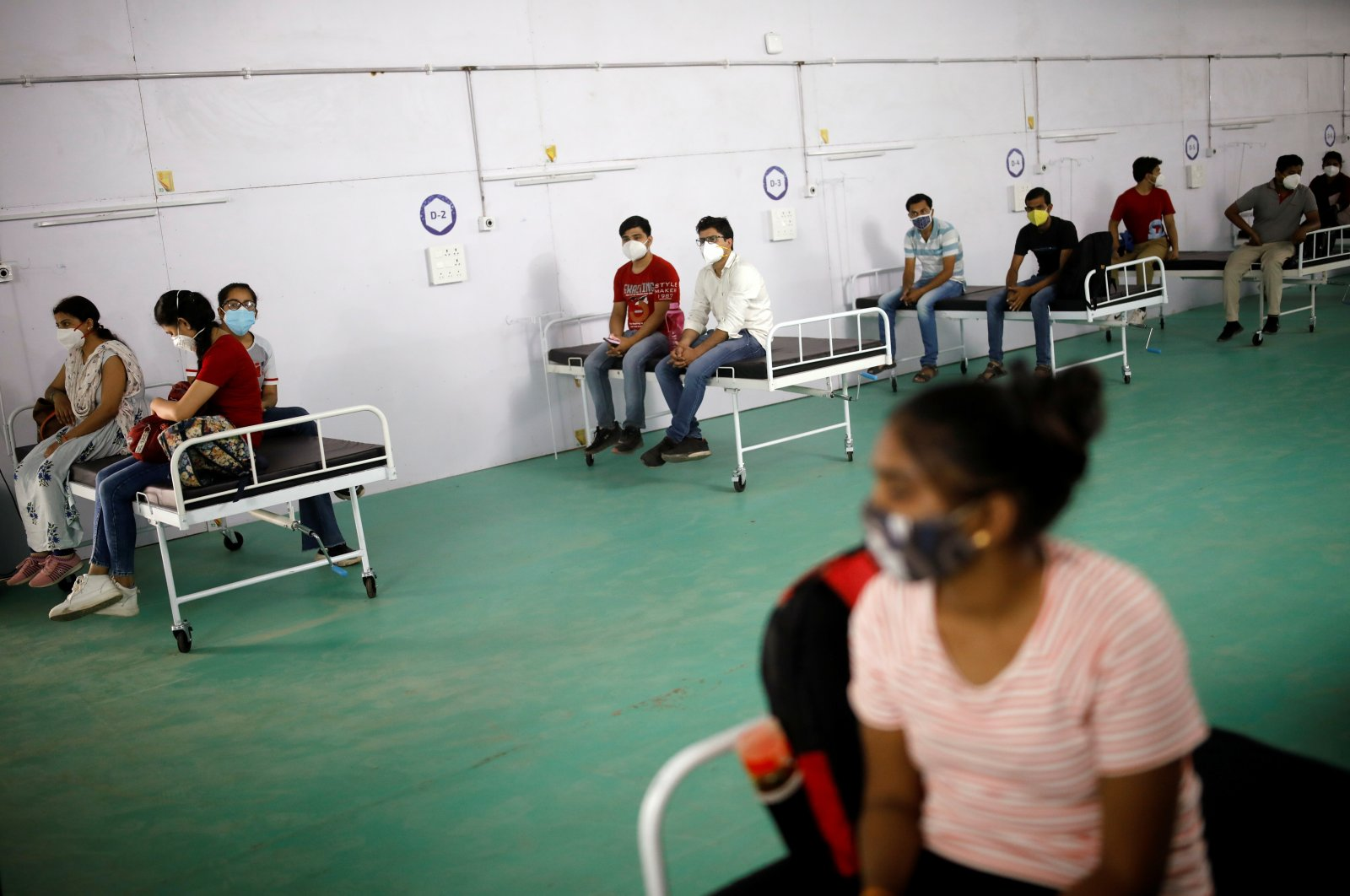 Medical workers sit on beds as they listen to a doctor during their briefing at the site of a temporary coronavirus care facility, at Ramlila Ground, in New Delhi, India, May 12, 2021. (Reuters Photo)