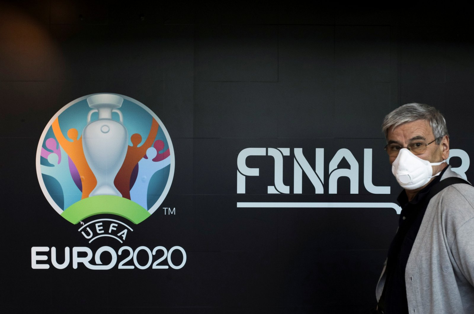A traveler in a protective facemask passes by a logo of the 2020 UEFA European Football Championship at Bucharest Henri Coanda International Airport, Otopeni, Romania, March 16, 2020. (Rueters Photo)