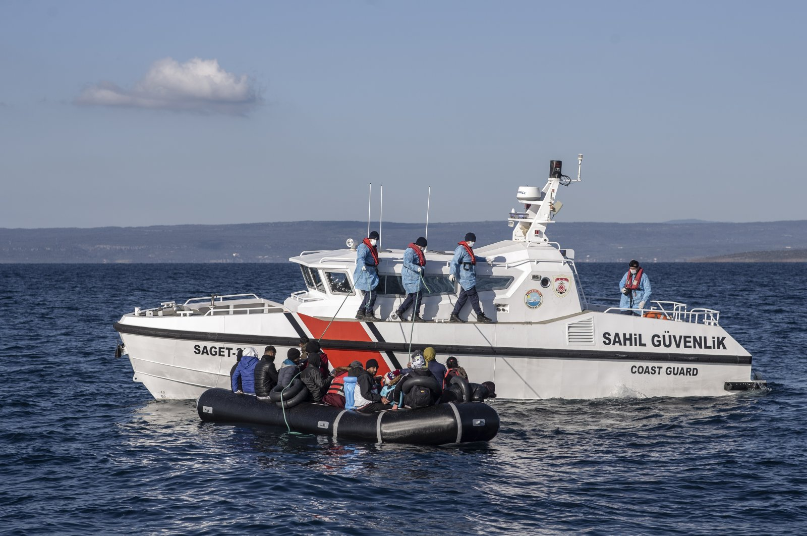 Members of the Turkish Coast Guard take migrants, who were allegedly pushed back from the Greece side, on a boat during a patrol to search and rescue migrants offshore the Ayvalık district in Balikesir, Turkey, 10 April 2021. (EPA Photo)