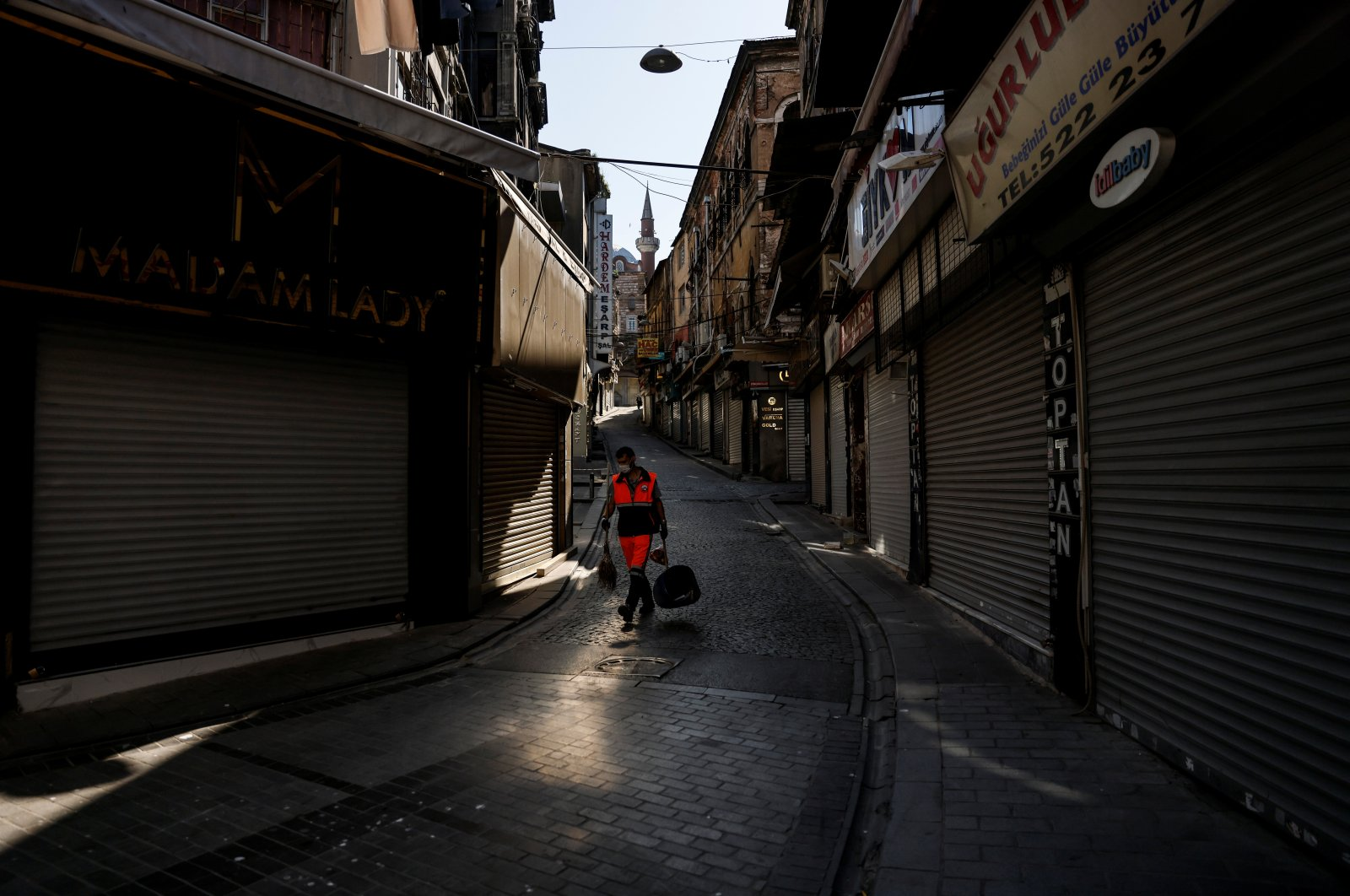 A municipality worker sweeps a street in otherwise busy Eminönü quarter, during lockdown, in Istanbul, Turkey, May 5, 2021. (REUTERS PHOTO)