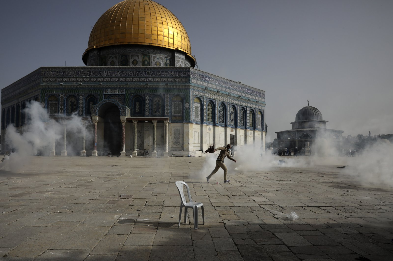 A Palestinian man runs away as Israeli police fire tear gas at the Al-Aqsa Mosque compound, East Jerusalem, occupied Palestine, May 10, 2021. (AP Photo)