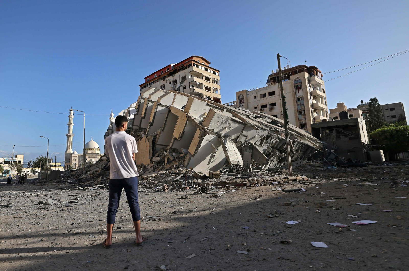A Palestinian man looks at a destroyed building in Gaza City, following a series of Israeli airstrikes on the Gaza Strip, Palestine, May 12, 2021. (AFP Photo)