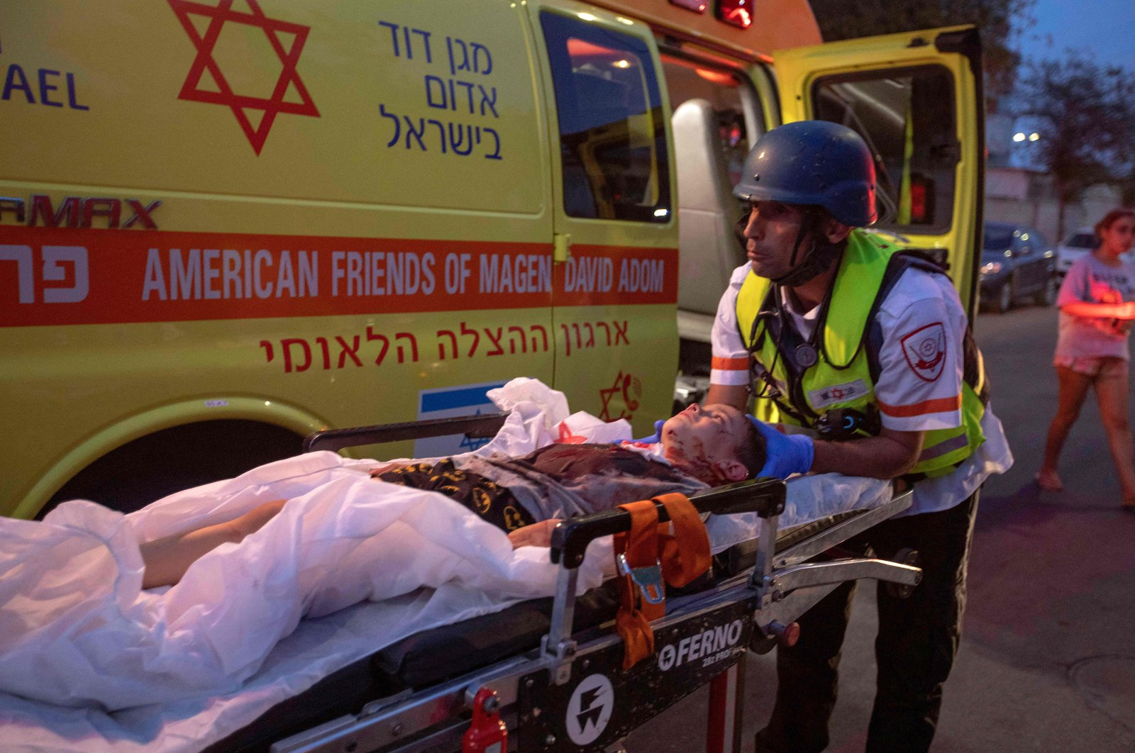 Rescue workers evacuate a an injured youngster by ambulance, amidst a rocket attack from the Gaza Strip, in the southern Israeli city of Sderot, on May 12, 2021. (AFP File Photo)