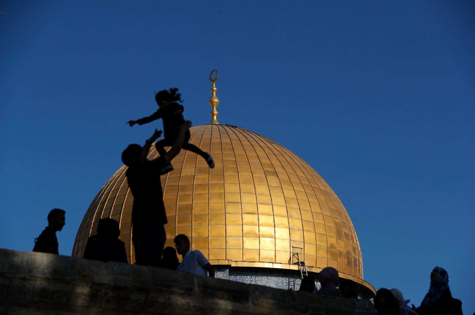 Muslim worshippers are silhouetted while celebrating in front of the Dome of the Rock mosque before the morning Ramadan Bayram prayer, which marks the end of the holy month of Ramadan, at the Al-Aqsa Mosques compound in Jerusalem, May 13, 2021. (AFP Photo)