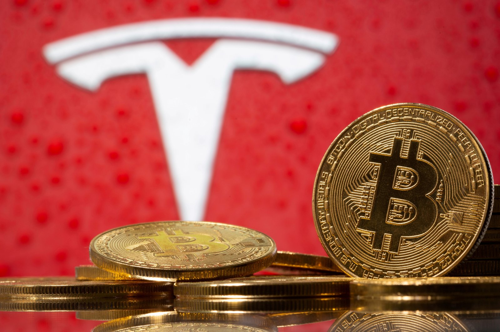 Representations of virtual currency Bitcoin are seen in front of Tesla logo in this illustration image, Feb. 9, 2021. (Reuters Photo)