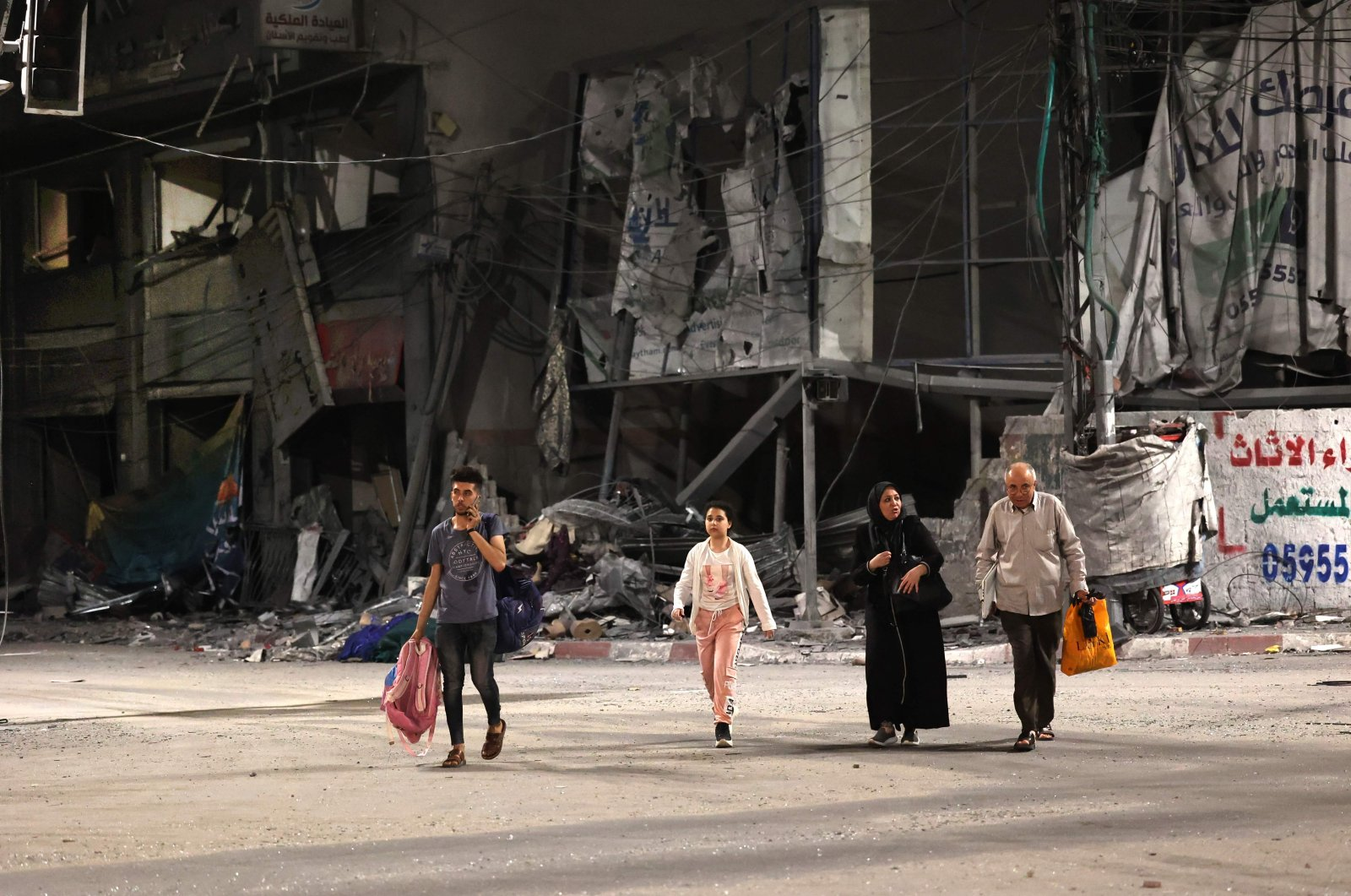 Palestinian families are pictured in a street after evacuating their homes east of Gaza City on May 13, 2021, due to heavy shelling by the Israeli military. (AFP Photo)