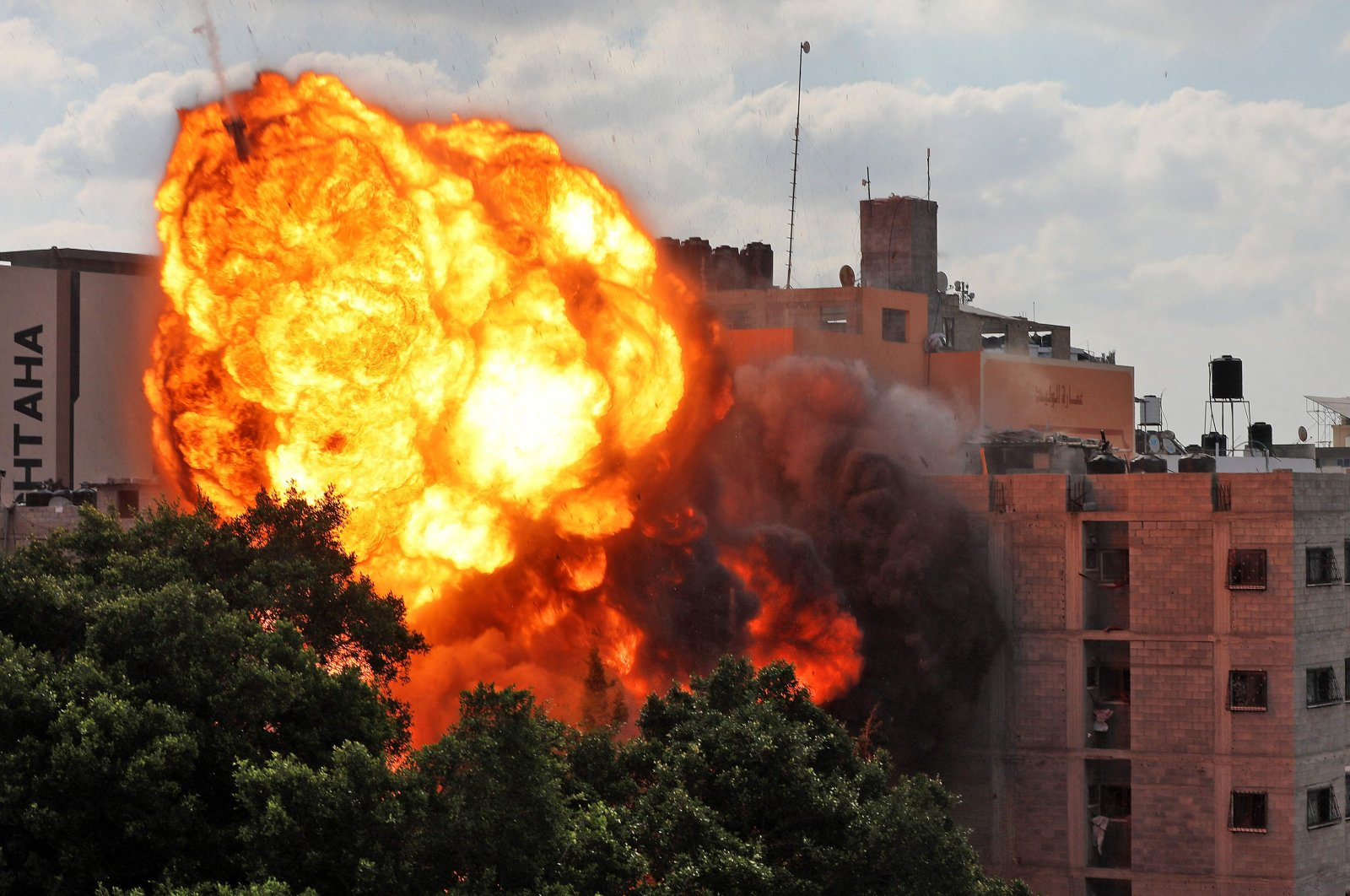 A ball of fire engulfs the Al-Walid building that was destroyed in an Israeli airstrike on Gaza city early in the morning, May 13, 2021. (AFP Photo)