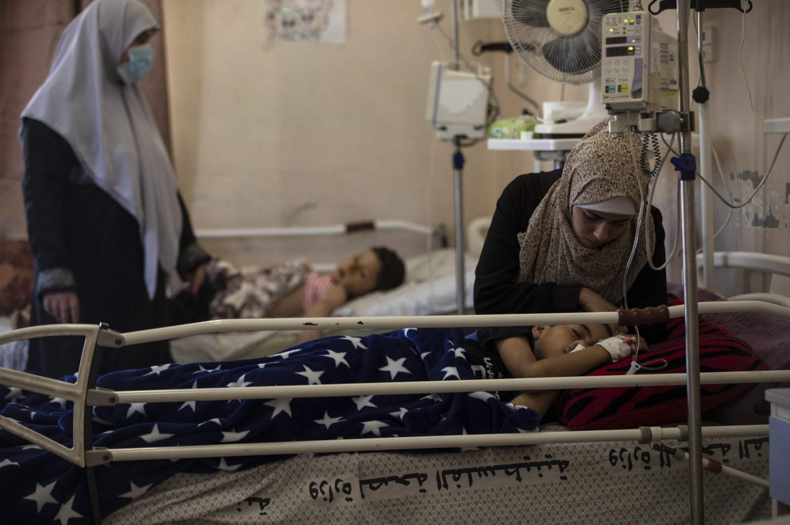 A mother comforts her child receiving treatment at the Shifa hospital in Gaza City, May 13, 2021. (AP Photo)