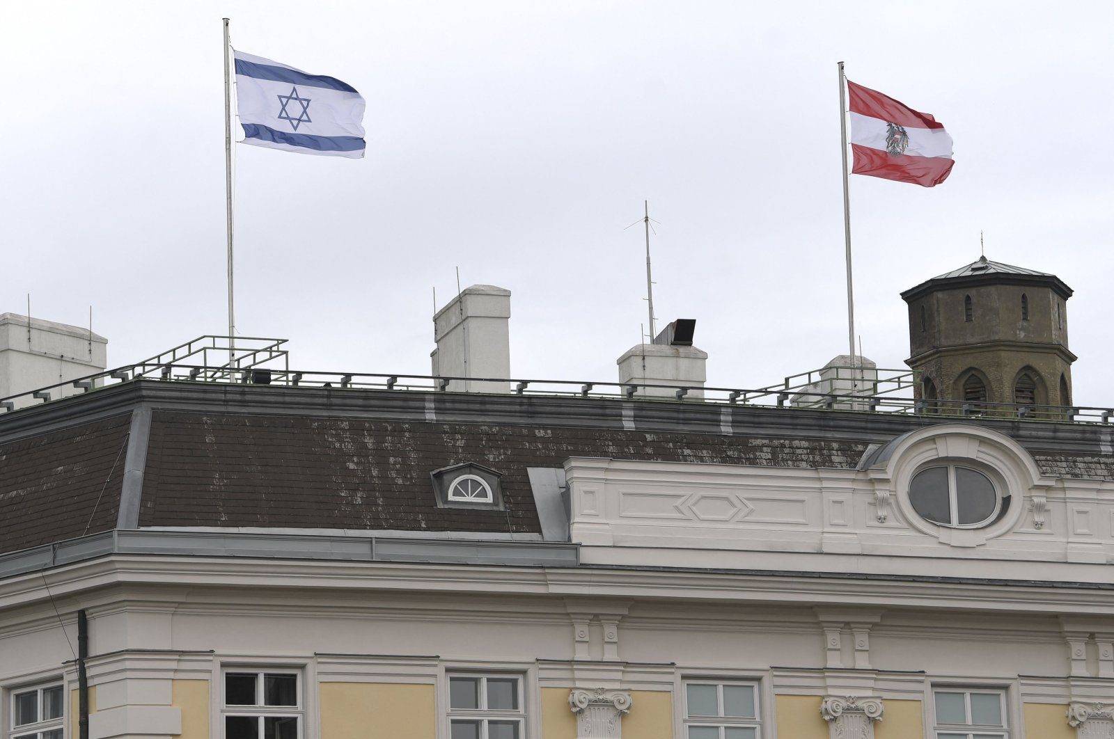 The Austrian Federal Chancellery raised the Israeli flag (L) as a sign of solidarity, in Vienna on May 14, 2021. (Helmut Fohringer/APA via AFP)