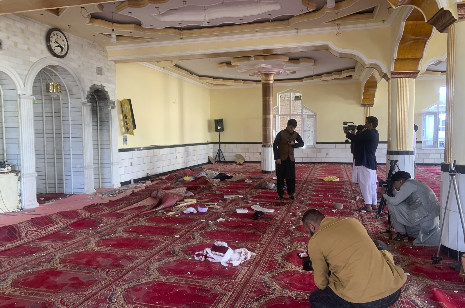 Afghan journalist take photos and film inside a mosque after a bomb explosion in Shakar Dara district of Kabul, Afghanistan, Friday, May 14, 2021. (AP Photo)