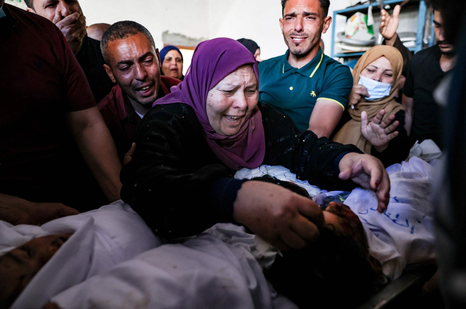The grandmother and relatives of three children from the Al-Tanani family, killed in an Israeli airstrike, mourn over their bodies, before their burial in Beit Lahya in northern Gaza Strip, Palestine, May 14, 2021. (AFP Photo)