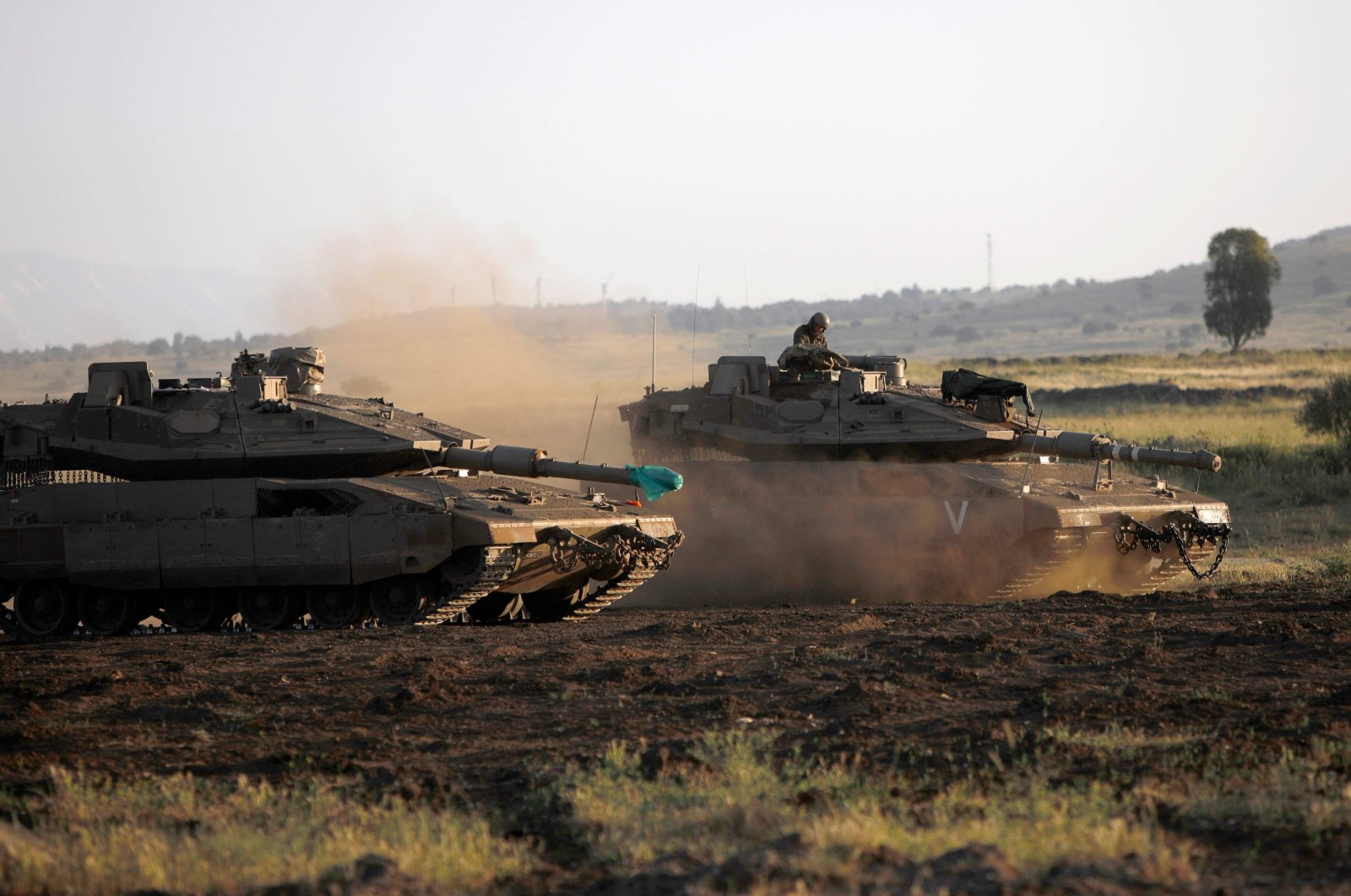 Israeli soldiers ride in Merkava Mark IV battle tanks near Moshav Alonei HaBashan in the Israeli-occupied Golan Heights, April 29, 2021. (AFP Photo)