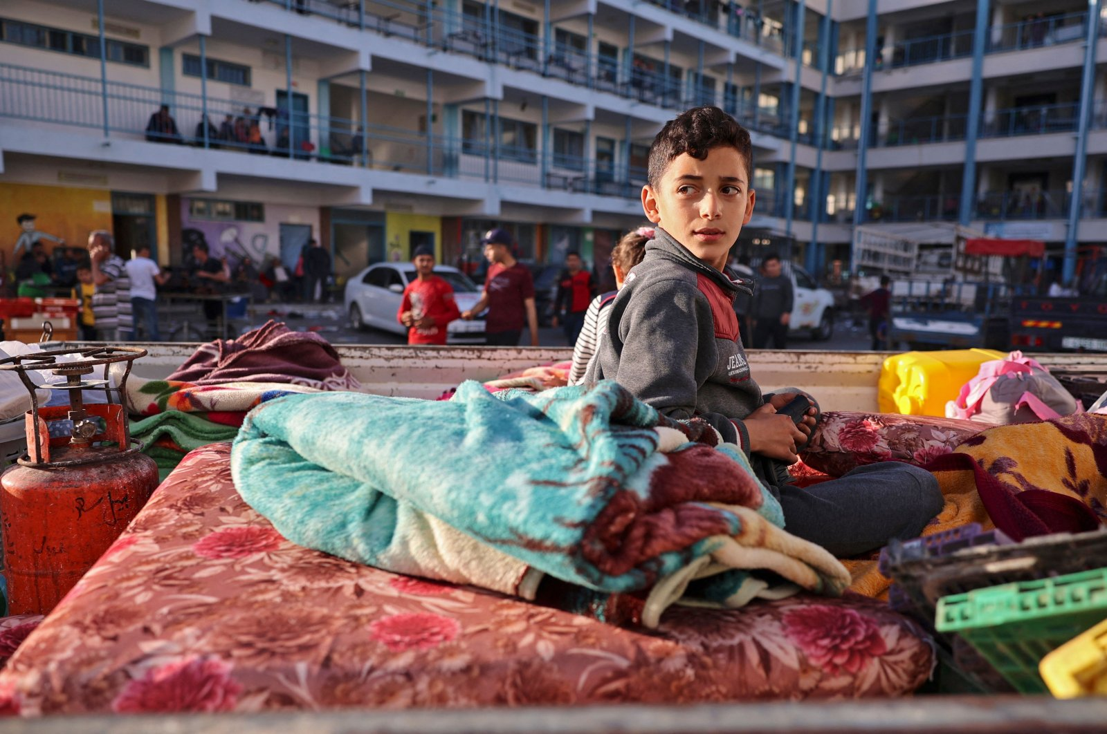 A Palestinian boy who fled his home due to Israeli air and artillery strikes sits on a mattress outside a school hosting refugees in Gaza City, Palestine, May 14, 2021. (AFP Photo)