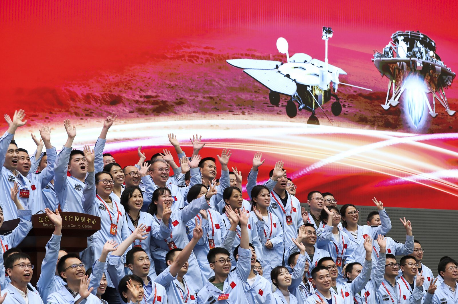 Members at the Beijing Aerospace Control Center celebrate after China's Tianwen-1 probe carrying the Zhurong rover successfully landed on Mars, Beijing, China, May 15, 2021. (AP Photo)