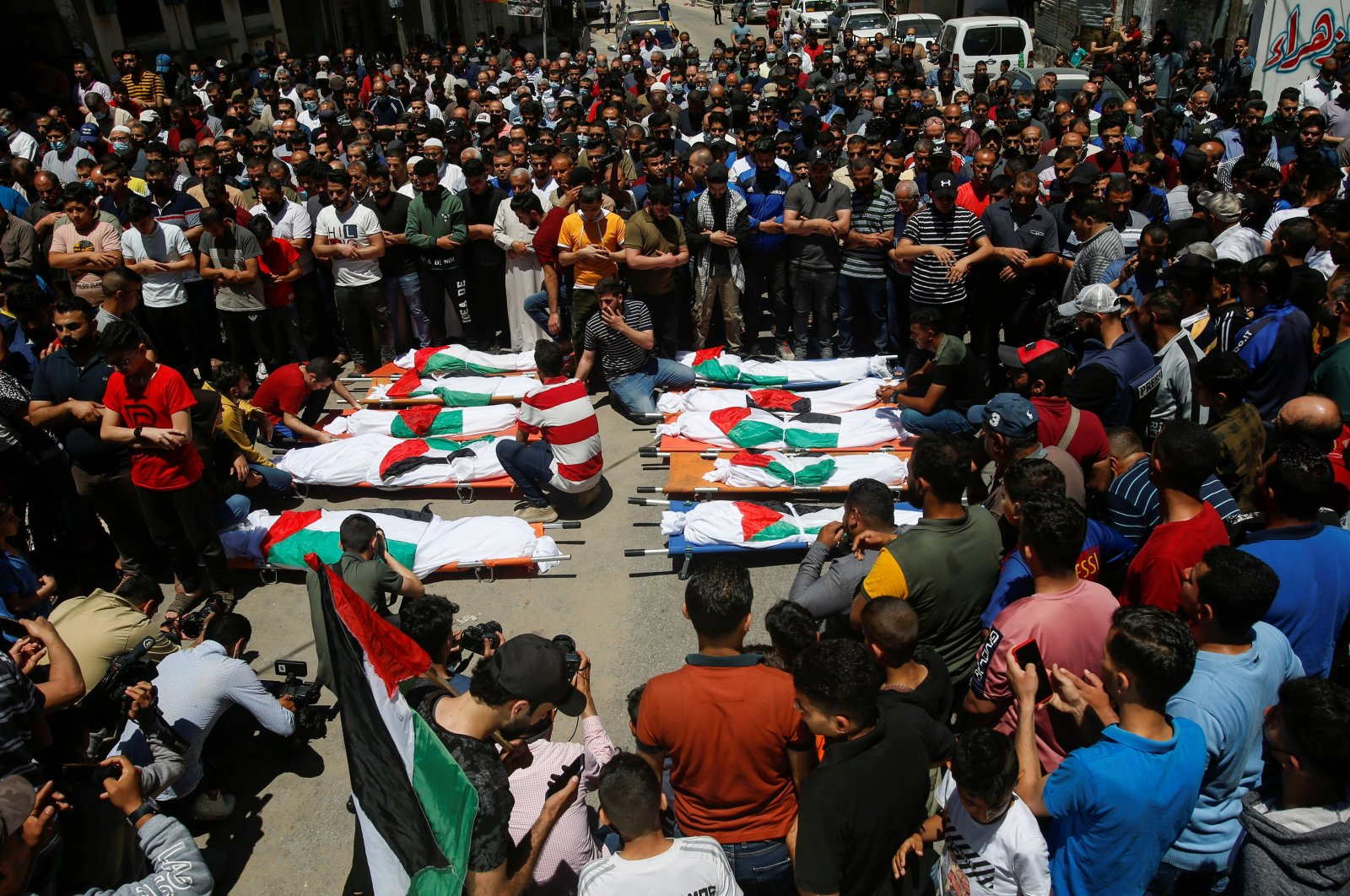 Mourners offer funeral prayers next to the bodies of Palestinians who were killed in an Israeli airstrike, in Gaza City, Palestine, May 15, 2021. (Reuters Photo)