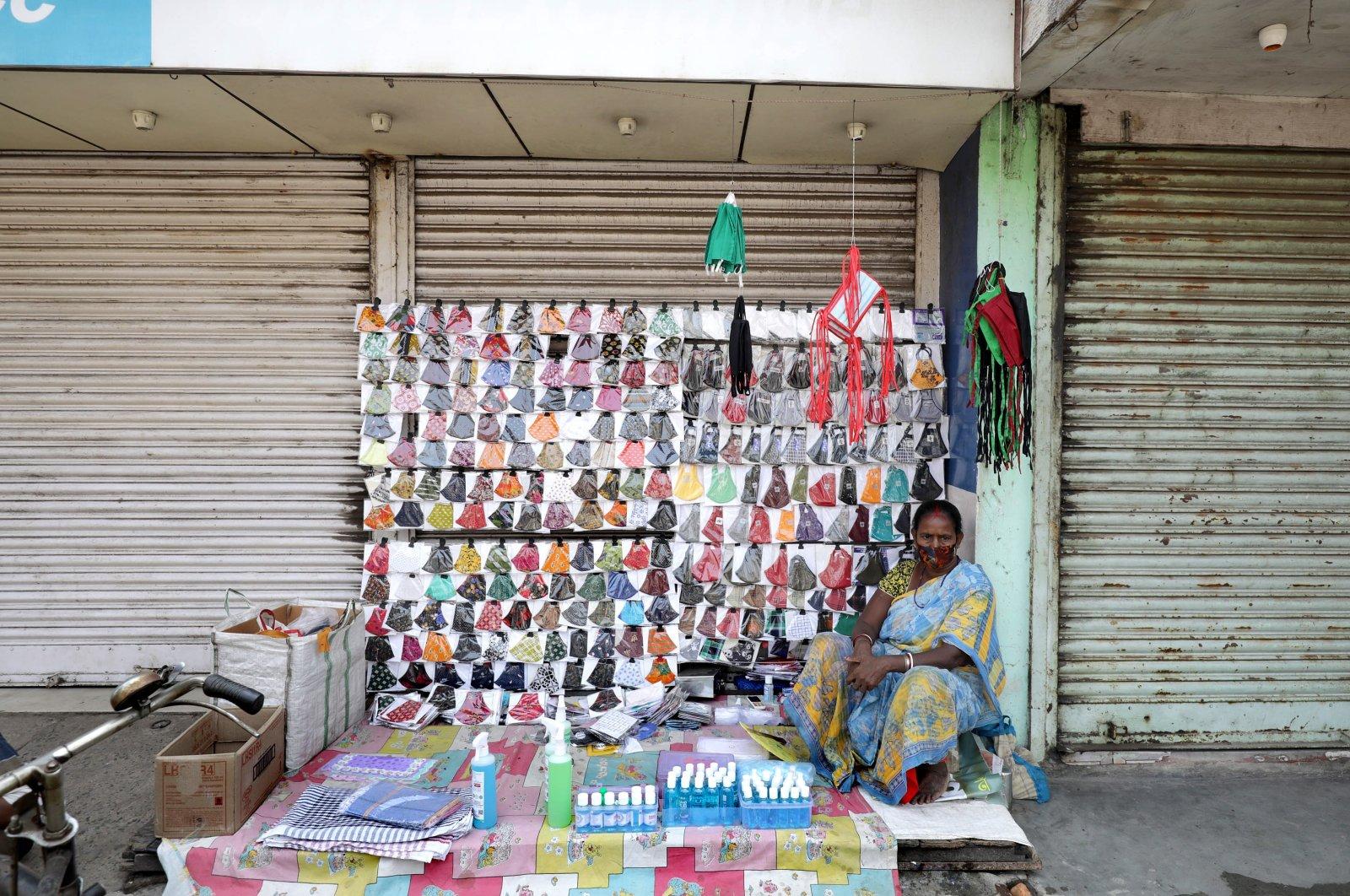 An Indian woman sells face masks near a closed market during the coronavirus pandemic far north of Kolkata, eastern India, May 12, 2021. (EPA Photo)