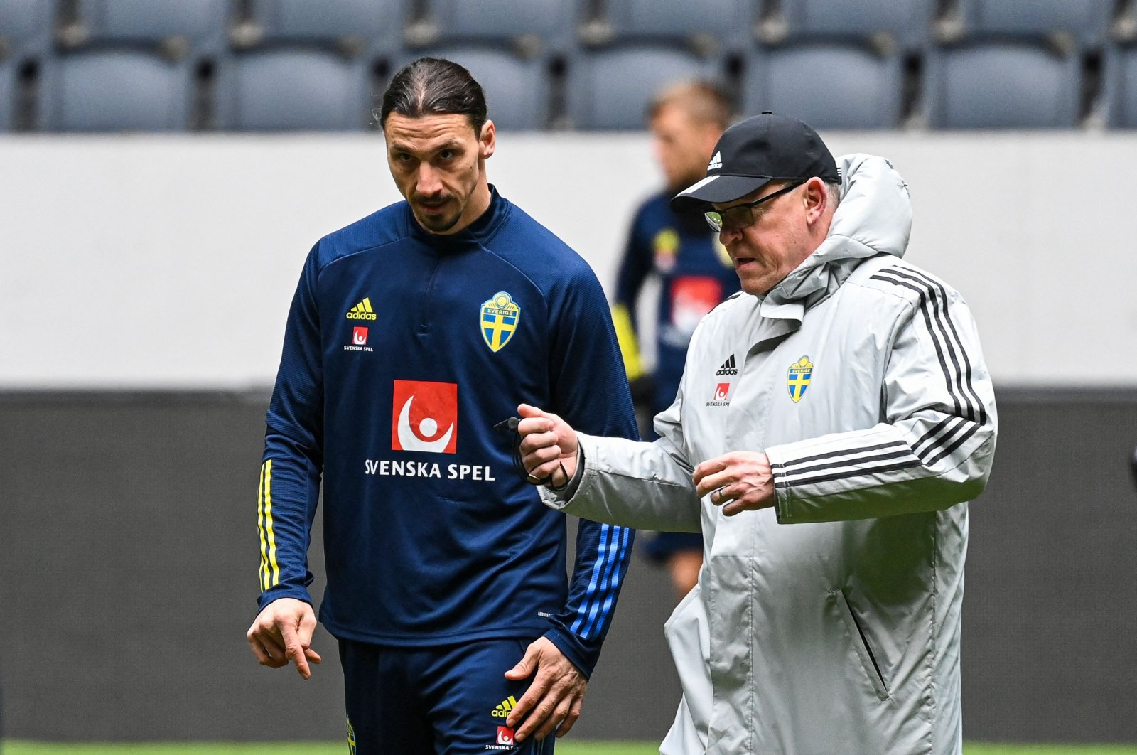 Sweden forward Zlatan Ibrahimovic (L) speaks with coach Janne Andersson during a training session of Sweden's national football team in Solna, Sweden, March 30, 2021. (AFP Photo)