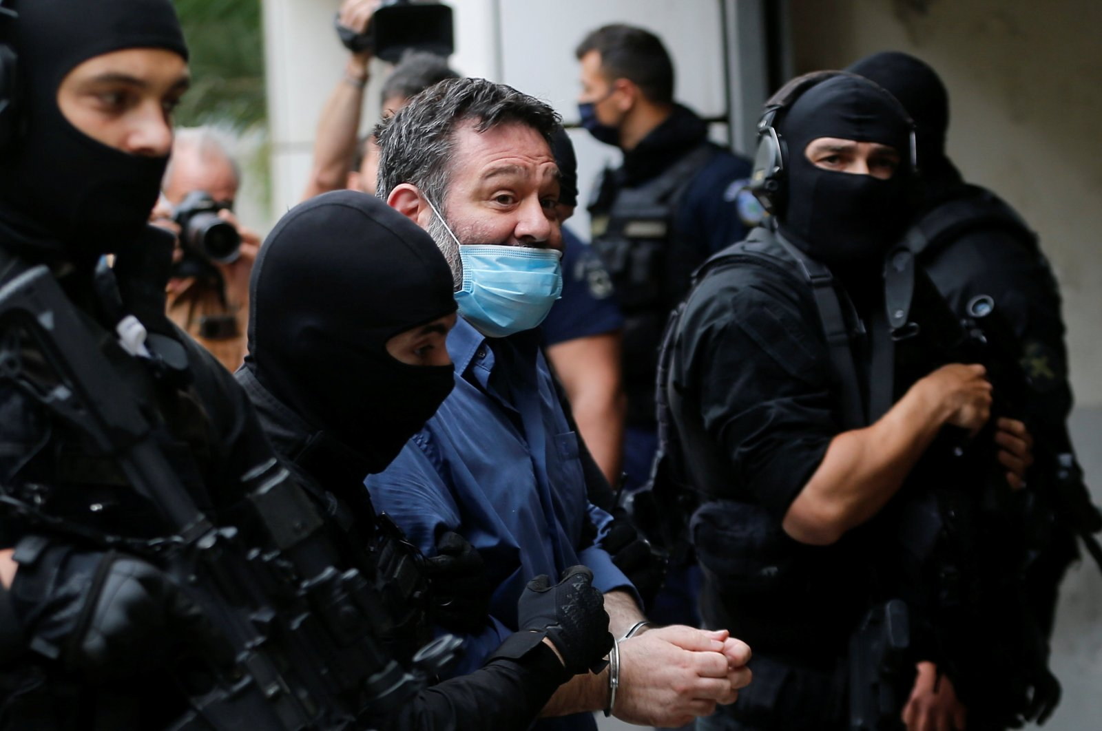 Ioannis Lagos (C), a Greek member of the European Parliament and former member of the far-right Golden Dawn party, is escorted by anti-terrorism police officers to the prosecutor's office in Athens, Greece, May 15, 2021. (REUTERS)