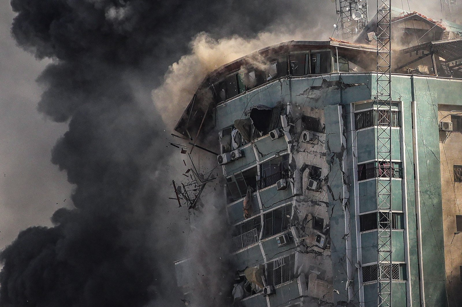 Smoke rises as a building collapses after an Israeli airstrike hits Al-Jalaa tower, which houses apartments and several media outlets, including The Associated Press and Al-Jazeera, in Gaza City, Palestine, May 15, 2021. (EPA Photo)