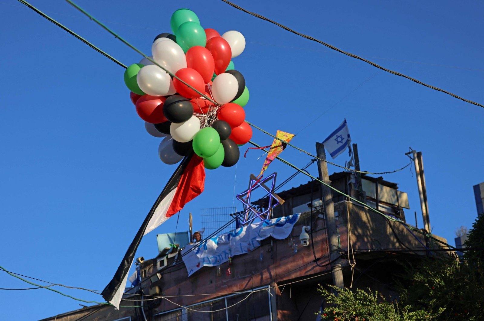 """A Palestinian flag attached to balloons is seen installed in front of the house of an Israeli settler on the 73rd anniversary of the nakba, the """"catastrophe,"""" of Israel's creation in 1948, Sheikh Jarrah, East Jerusalem, occupied Palestine, May 15, 2021. (AFP Photo)"""