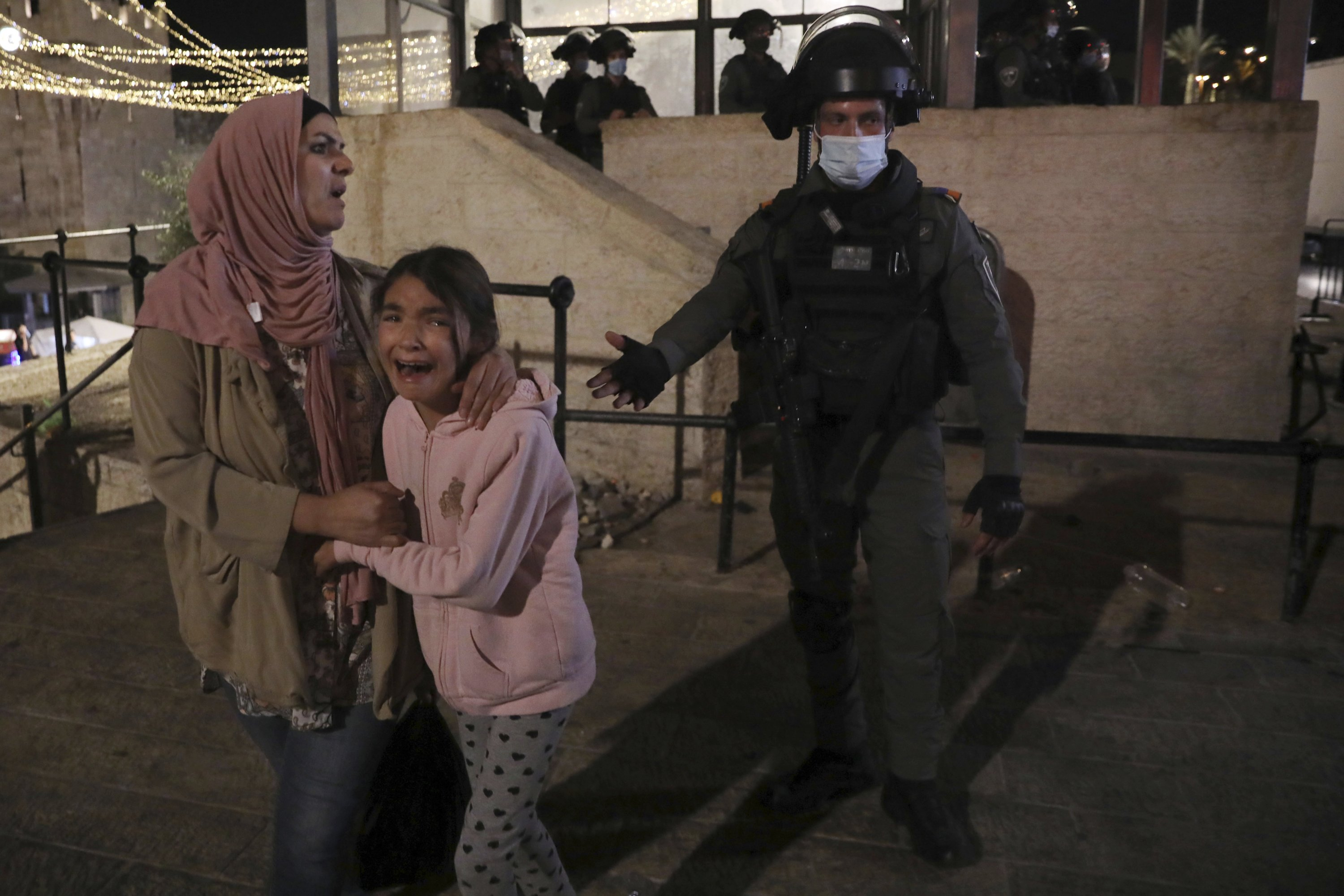 An Israeli police officer gestures to a Palestinian woman and her daughter, frightened by Israeli attacks to the outside of the Old City, East Jerusalem, occupied Palestine, May 11, 2021. (AP Photo)