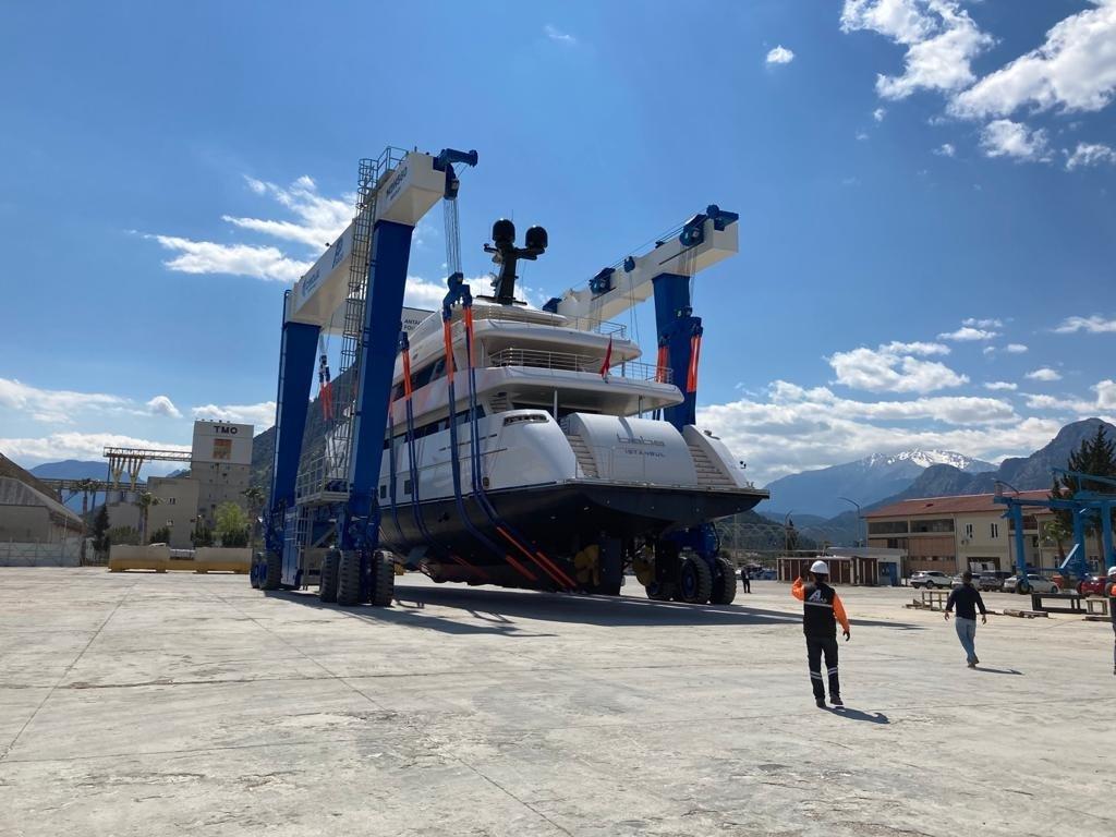 A travel lift (crane) prepares to launch a yacht produced in Antalya Free Zone, Antalya, southern Turkey, May 16, 2021. (Photo by ASBAŞ via AA)