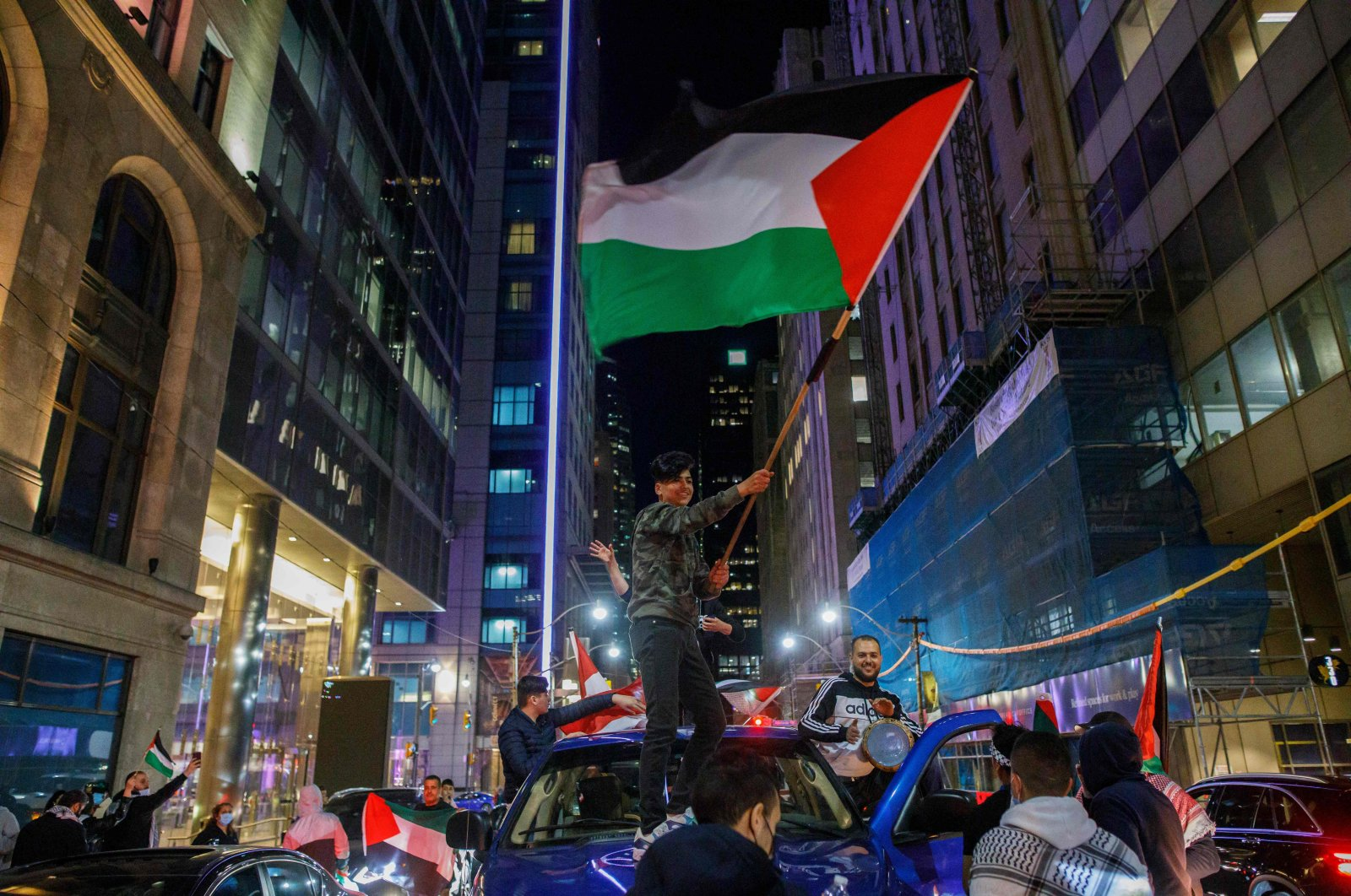 People wave flags atop cars in traffic during a demonstration to voice support for the people of Palestine, at Toronto City Hall in Toronto, Ontario, Canada, on May 15, 2021. (AFP Photo)