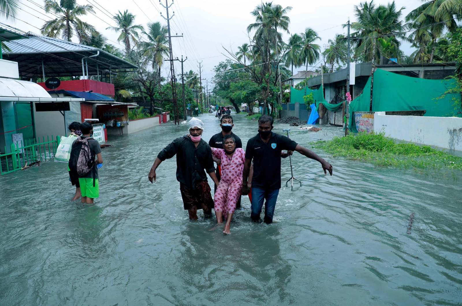 Police and rescue personnel evacuate a local resident through a flooded street in a coastal area after heavy rains under the influence of cyclone 'Tauktae' in Kochi, India, May 14, 2021. (AFP Photo)