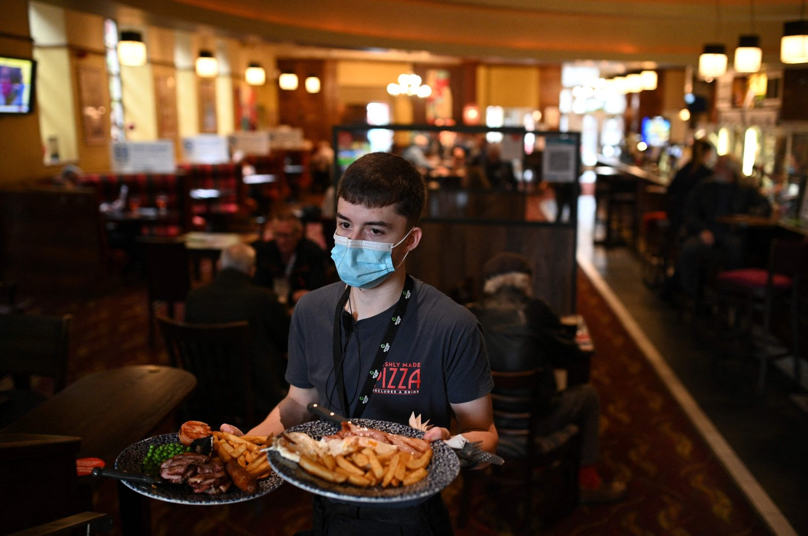 A member of the bar staff serves food in a Wetherspoons pub in Leigh, Greater Manchester, northwest England, Oct. 22, 2020. (AFP Photo)