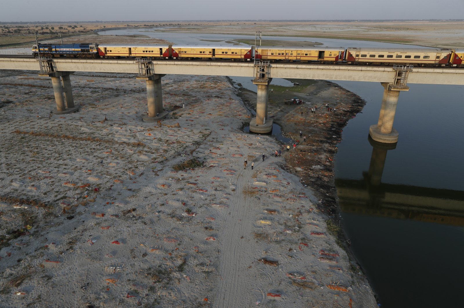 Several bodies are seen buried in shallow graves on the banks of Ganges river in Prayagraj, India. Saturday, May 15, 2021. (AP Photo)