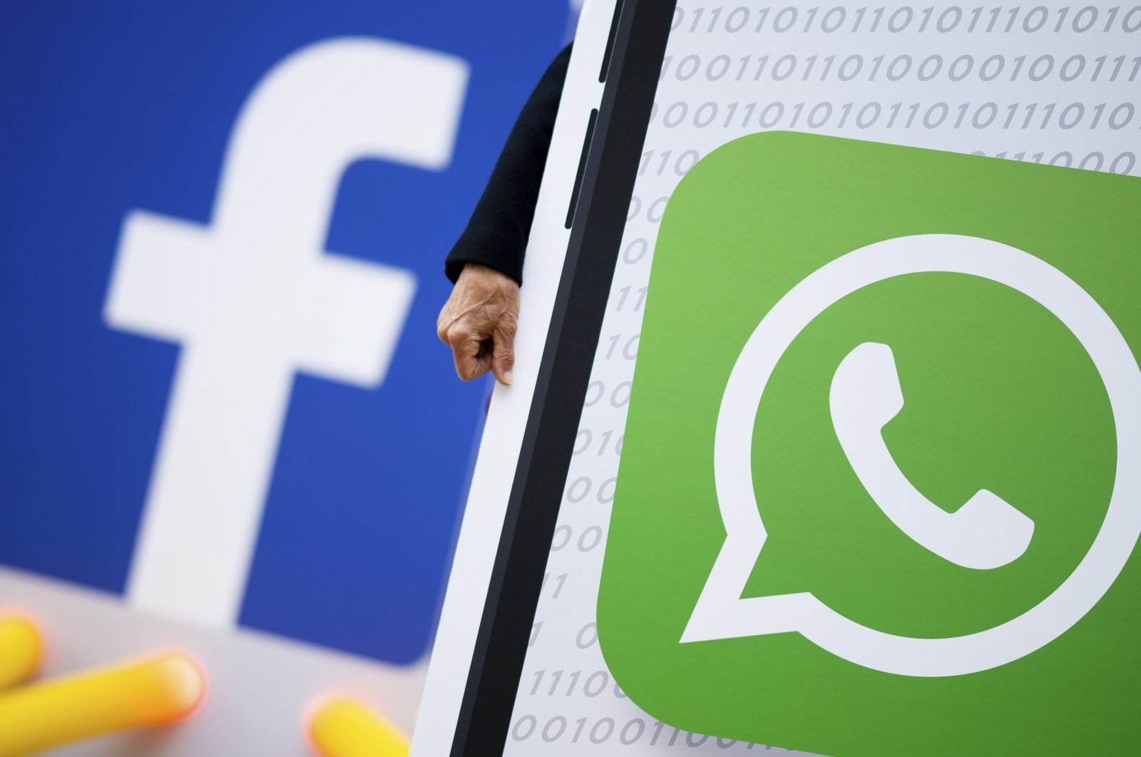 """Activists of the campaign network Campact demonstrate against new terms of use of the communication app """"WhatsApp"""" in front of the Hamburg HQ of internet company Facebook, Hamburg, Germany, Friday, May 14, 2021. (AP Photo)"""