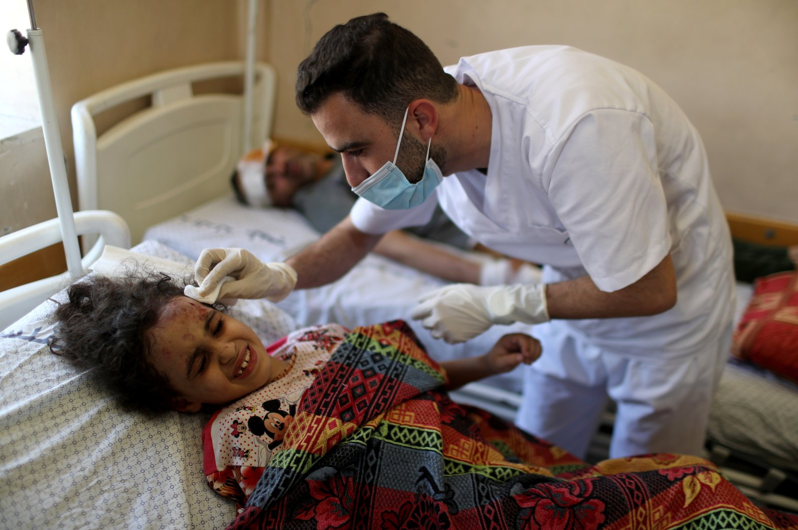 Palestinian girl Suzy Eshkuntana, 6, is treated by a medic at a hospital after being pulled from the rubble of a building amidst Israeli airstrikes, in Gaza City on May 16, 2021. (Reuters Photo)