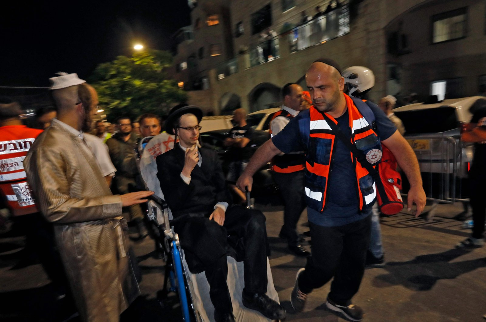 Israeli medics evacuate an injured an ultra-Orthodox Jewish man after the collapse of grandstand seating at a synagogue in the Israeli settlement of Givat Zeev in the occupied West Bank outside Jerusalem, on May 16, 2021. (AFP Photo)