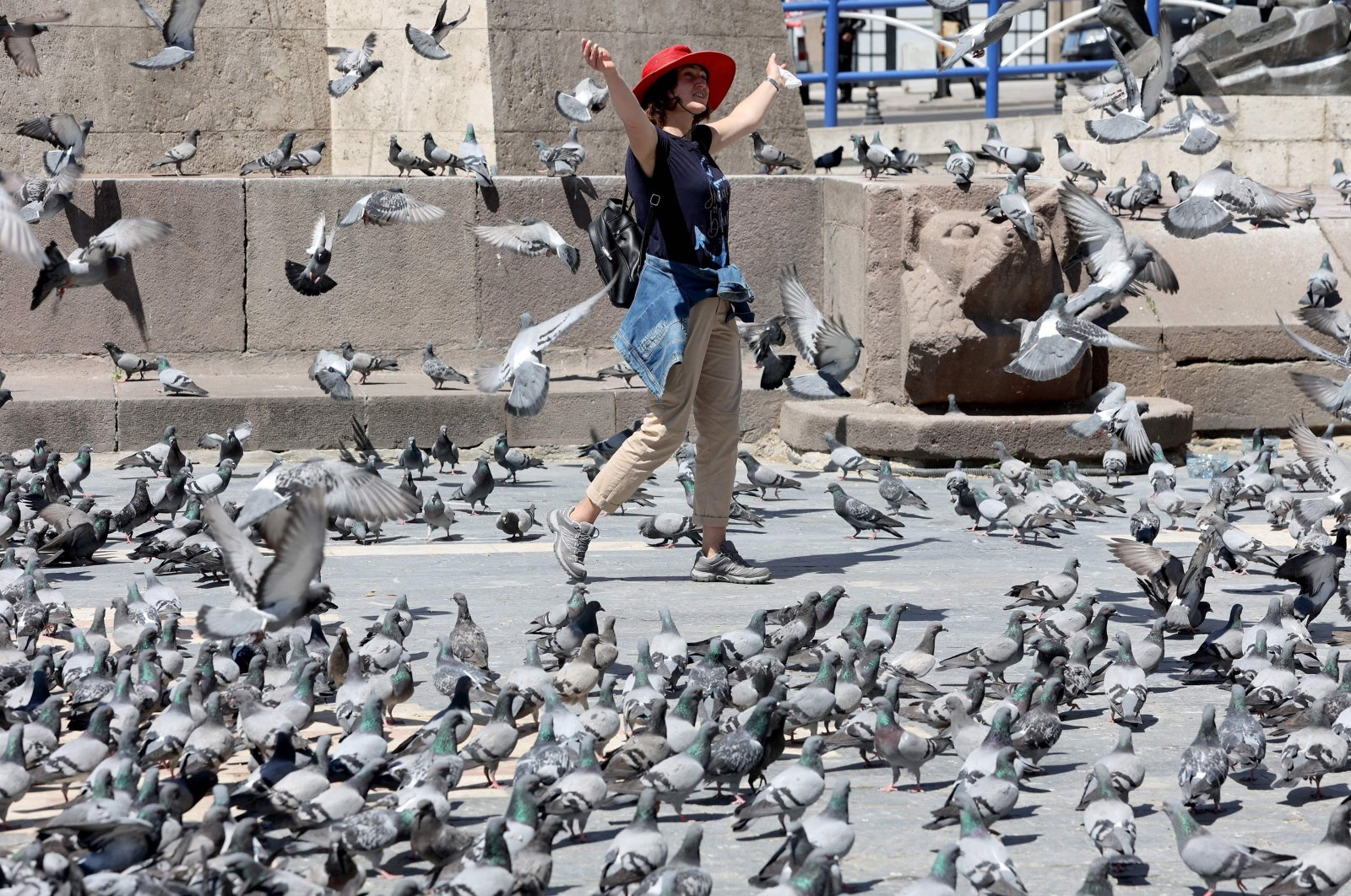 A woman enjoys making a kit of pigeons fly in Ankara as Turkeyentered a complete lockdown until May 17 to prevent the spread of coronavirus, Ankara, Turkey. (AFP Photo)