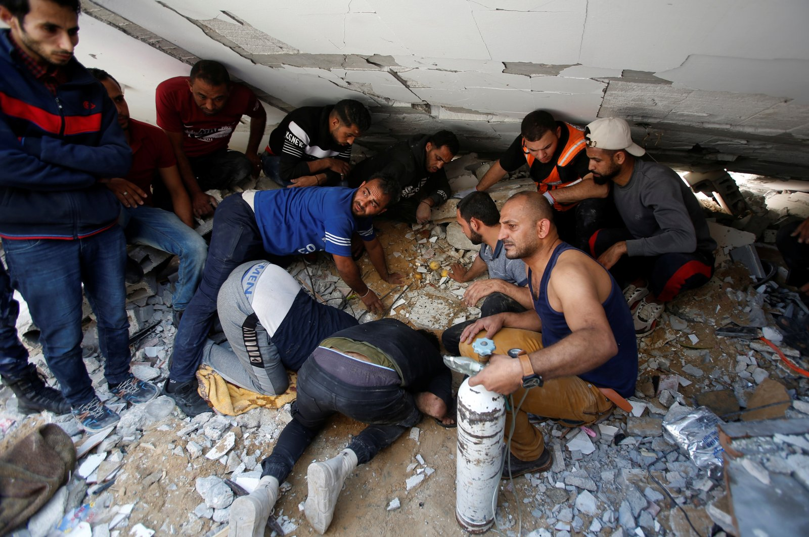 Rescuers search for people in the rubble of a building at the site of Israeli airstrikes, in Gaza City, May 16, 2021. (Reuters Photo)