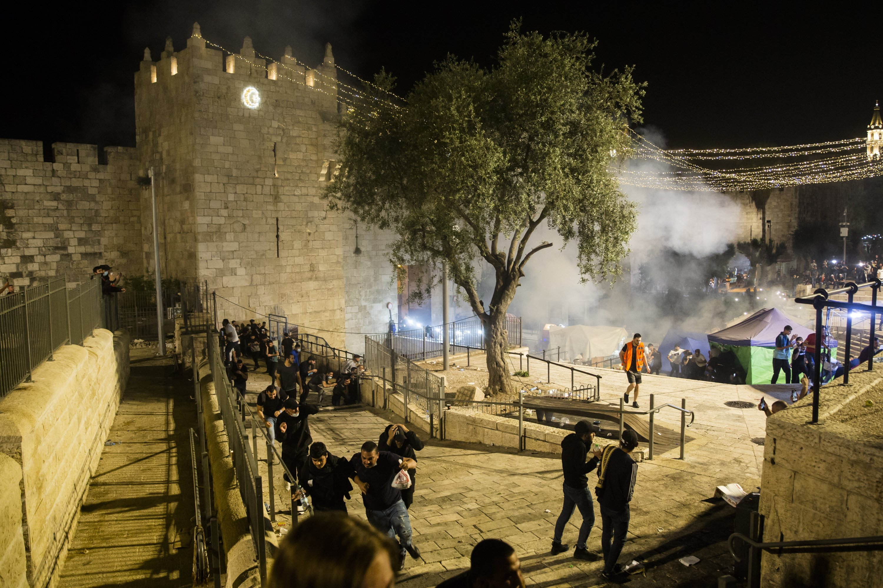 Palestinians escape from a stun grenade fired by Israeli forces at Damascus Gate during the Islamic holy month of Ramadan, in Old City, East Jerusalem, occupied Palestine, May 8, 2021. (Photo by Getty Images)