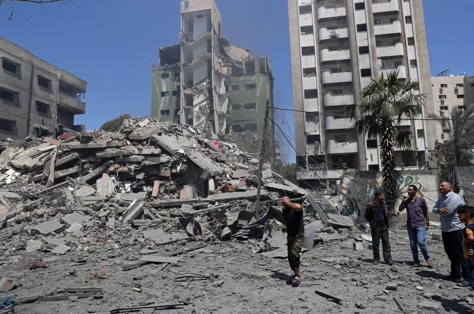 People inspect the rubble of a destroyed residential building that was hit by an Israeli airstrike, in Gaza City, Palestine, May 16, 2021. (AP Photo)