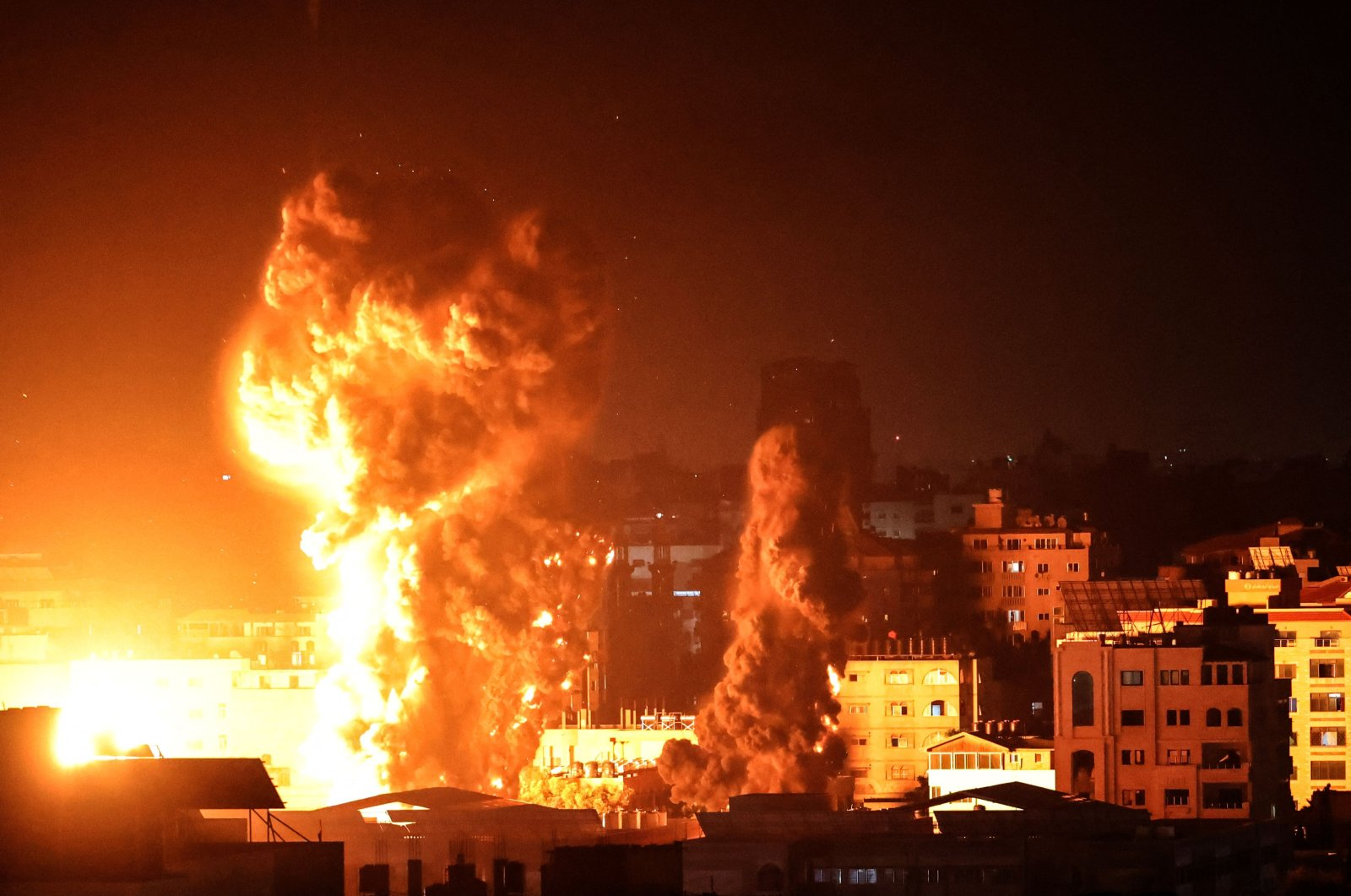 Fire and smoke rise above buildings in Gaza City as Israeli warplanes target the Palestinian enclave, Gaza City, Palestine, early on May 17, 2021. (AFP Photo)