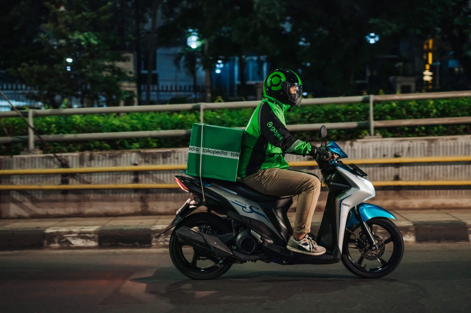 This undated handout photo received from GoTo Group shows a Gojek rider delivering a Tokopedia package to a customer in Jakarta, Indonesia, May 17, 2021. (AFP Photo)